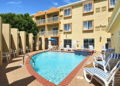 Outdoor pool with sundeck | Comfort Suites DFW Airport