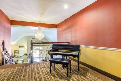 Sitting area and piano on second floor | Quality Suites North