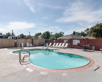 Outdoor pool with hot tub and sundeck | Quality Suites