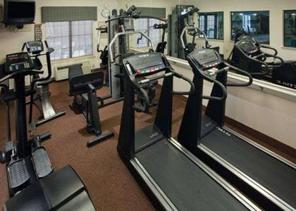 Exercise room with cardio equipment and weights   Quality Inn & Suites, Near University