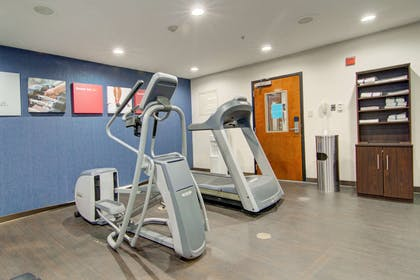Exercise room with cardio equipment and weights   Comfort Suites Airport