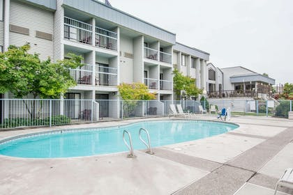 Outdoor pool in garden setting | Quality Inn Conference Center