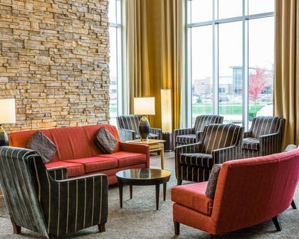 Relax in the open space lobby with club-lounge seating | Cambria Hotel Appleton