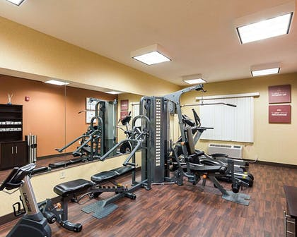 Exercise room with cardio equipment and weights | Comfort Suites Airport