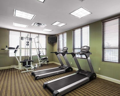 Exercise room with cardio equipment and weights | Quality Inn