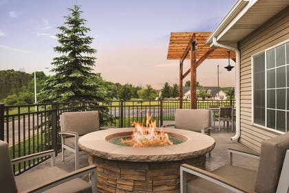 Outdoor Seating Area with Fireplace | Country Inn & Suites by Radisson, West Bend, WI