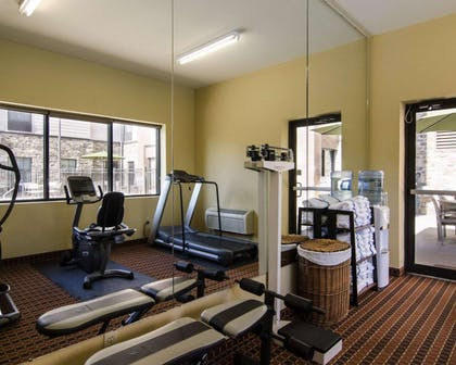 Fitness center with cardio equipment and weights | MainStay Suites Rogers near I-49