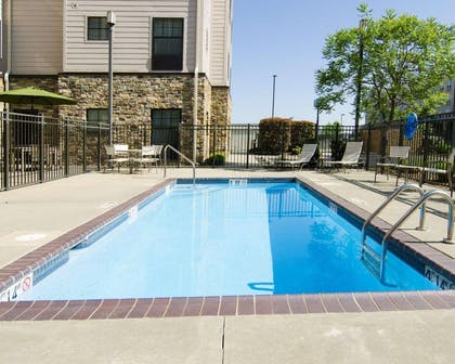 Outdoor pool with sundeck | MainStay Suites Rogers near I-49