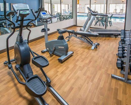 Exercise room with cardio equipment and weights | Comfort Suites University Area
