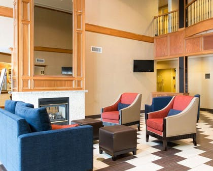 Relax by the fireplace in the lobby | Comfort Suites Benton Harbor - St. Joseph