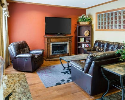 Relax by the fireplace in the lobby | Quality Inn