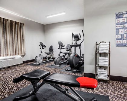 Fitness center with cardio equipment and weights | Quality Inn & Suites Kansas City Airport North