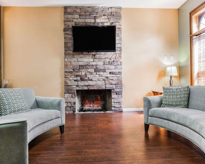 Relax by the fireplace in the lobby | Quality Inn & Suites Kansas City Airport North