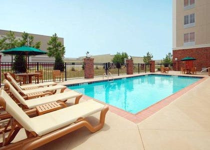 Outdoor pool with sundeck | Comfort Suites Airport